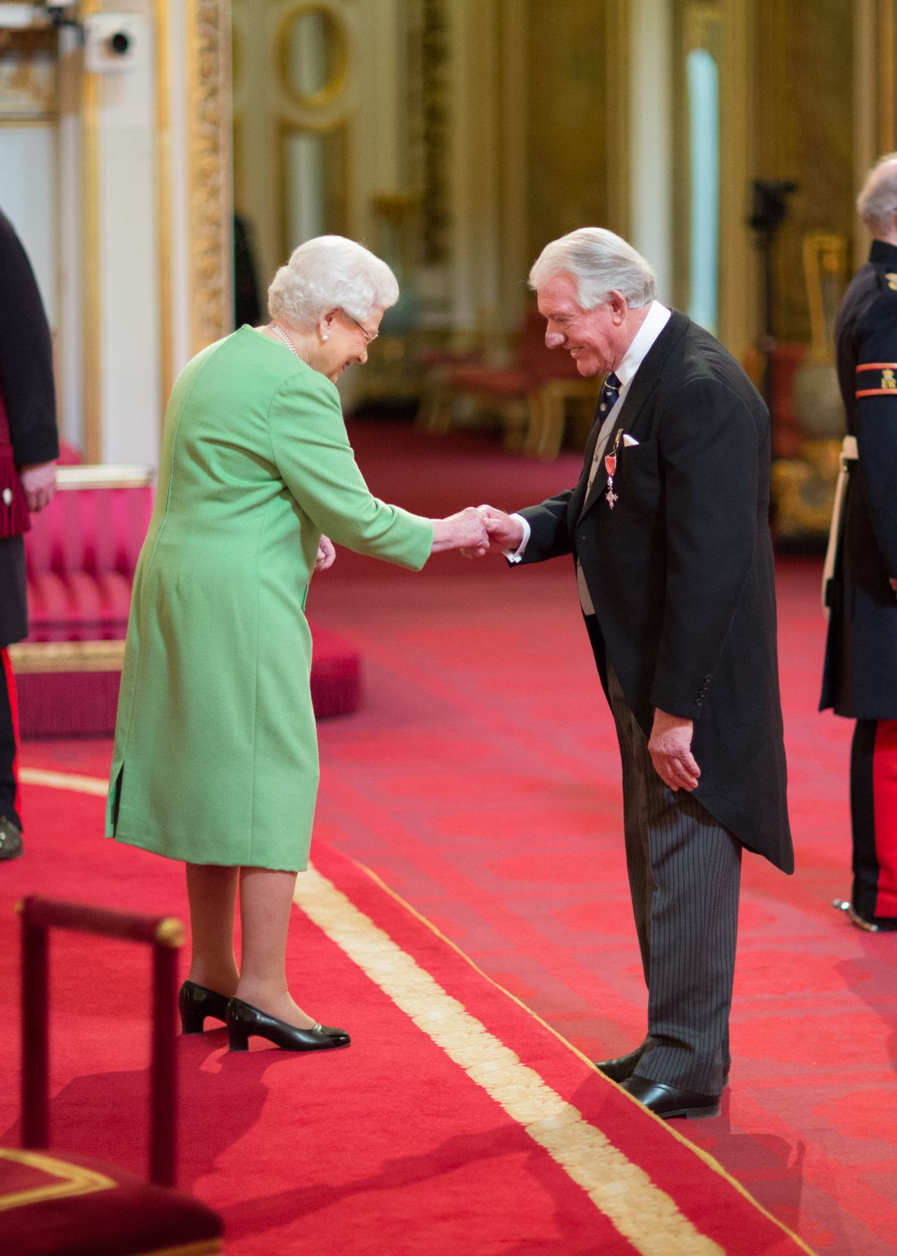 Angus receiving MBE from Queen Elizabeth II - credit - Image courtesy of British Ceremonial Arts Limited.